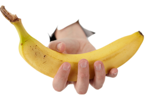 hand from a hole is holding a banana
