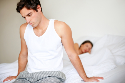 Portrait of unhappy young man sitting seperately while his wife sleeping on bed