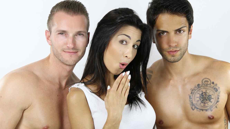 mujer-con-blusa-blanca-en-medio-de-un-hombre-blanco-y-rubio-y-de-otro-tipo-moreno